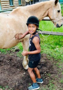 Kurland children learning how to groom the horses